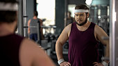 Unhappy overweight man looking at his mirror reflection in gym, diet and sport