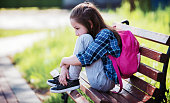 Sad schoolgirl sitting in the park. Education, lifestyle concept