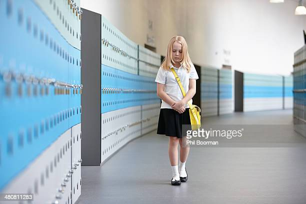 Unhappy schoolgirl walking alone in school corridor