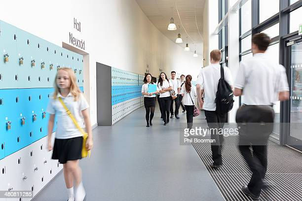Unhappy schoolgirl walking in school corridor