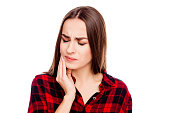 Unhappy sick woman having toothache and touching cheek