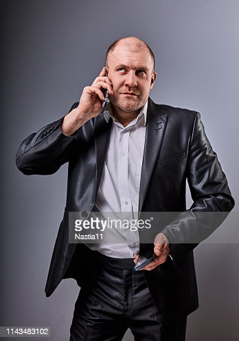 Unhappy stressed angry business man talking on mobile phone very emotional in office suit and looking up on grey studio background. Closeup : Stock Photo
