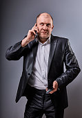 Unhappy stressed angry business man talking on mobile phone very emotional in office suit and looking up on grey studio background. Closeup portrait