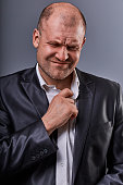 Unhappy stressed bald angry business man pulling the shirt collar with very bad emotions in office suit on grey studio background. Closeup portrait