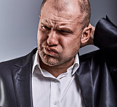 Unhappy stressed bald angry business man to scratching the head with very bad emotions in office suit on grey studio background. Closeup toned face portrait
