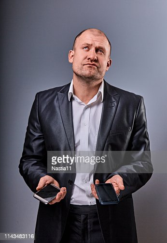 Unhappy stressed tired business man holding two mobile phones in hands and looking up in office suit on grey studio background. Closeup : Stock Photo