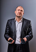 Unhappy stressed tired business man holding two mobile phones in hands and looking up in office suit on grey studio background. Closeup portrait