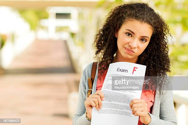 Unhappy Student Holding Exam Result With F Grade On Sidewalk