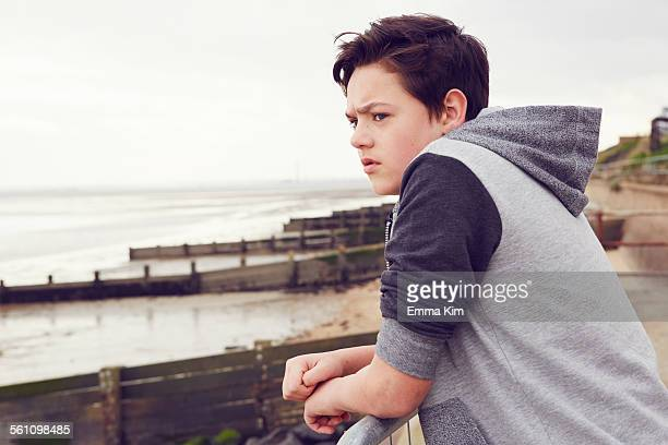 Unhappy teenage boy looking out from railings, Southend on Sea, Essex, UK