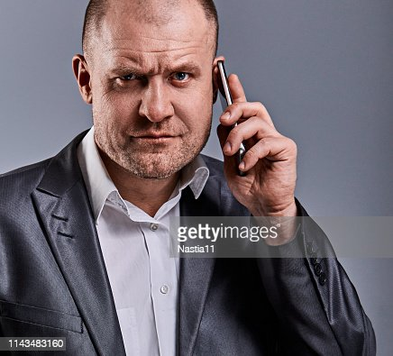Unhappy tired angry business man talking on mobile phone and holding in hand one more phone in office suit on grey studio background. toned face portrait : Stock Photo