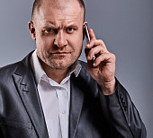 Unhappy tired angry business man talking on mobile phone and holding in hand one more phone in office suit on grey studio background. Closeup toned face portrait