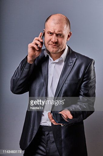 Unhappy tired angry business man talking on mobile phone and holding in hand one more phone in office suit on grey studio background. Closeup : Stock Photo