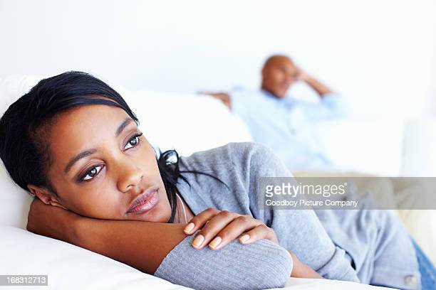 Unhappy woman lying in couch
