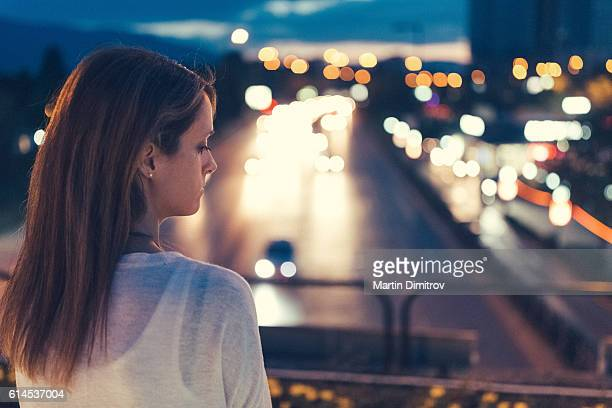 Unhappy woman sitting alone at the bridge