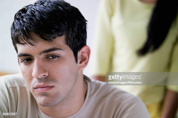 Unhappy young man with unknown woman in background, close-up, selective focus, focus on man