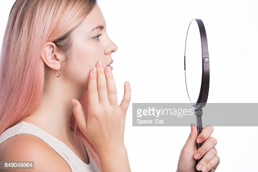 Unhappy young pretty girl looking at her pimple on her face in the mirror : Stock Photo