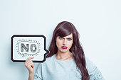 """Portrait of young woman wearing grey jumper, holding a speech bubble with word """"no"""". Studio shot, white background."""