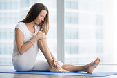 Unhappy young woman sitting on the mat, grabbing an ankle, unable to start yoga work out because of sport injury, feeling pain. Beginner doing wrong exercise without coacher