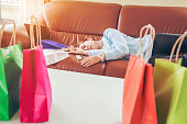 Unhappy young woman sleep on sofa and hold shopping bags with debit card bankruptcy for shopping online