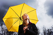 Unhappy young woman with umbrella waits for storm to pass