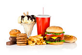 Group of unhealthy food isolated on white background. The composition includes, candy bar, muffin, cookies, ice cream, french fries, a glass of soda, hamburger and a hot dog. This is an unhealthy food
