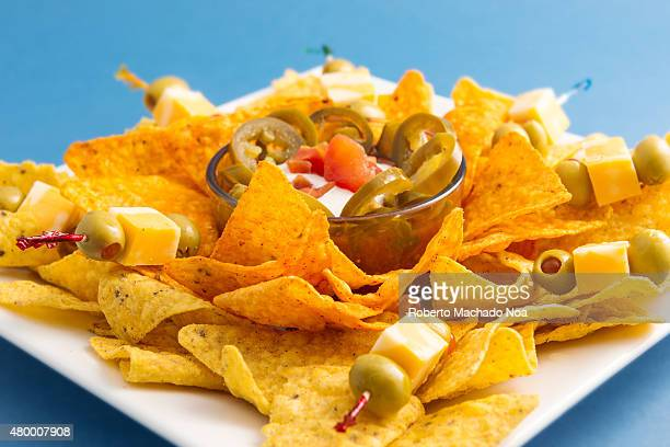 Unhealthy high calories food Spicy mexican nachos over a blue background Delicious junk food Special for a snack while drinking beer