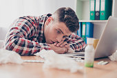 Unhealthy manager with high temperature lying on working table