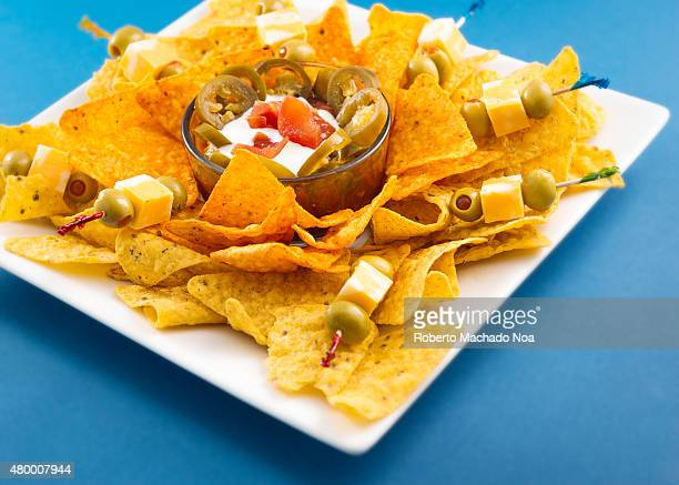 Unhealthy snack for drinking Spicy mexican nachos over a blue background Delicious junk food Special for a snack while drinking beer