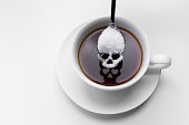 unhealthy white sugar concept. Scull spoon with sugar and cup of black coffee on white background