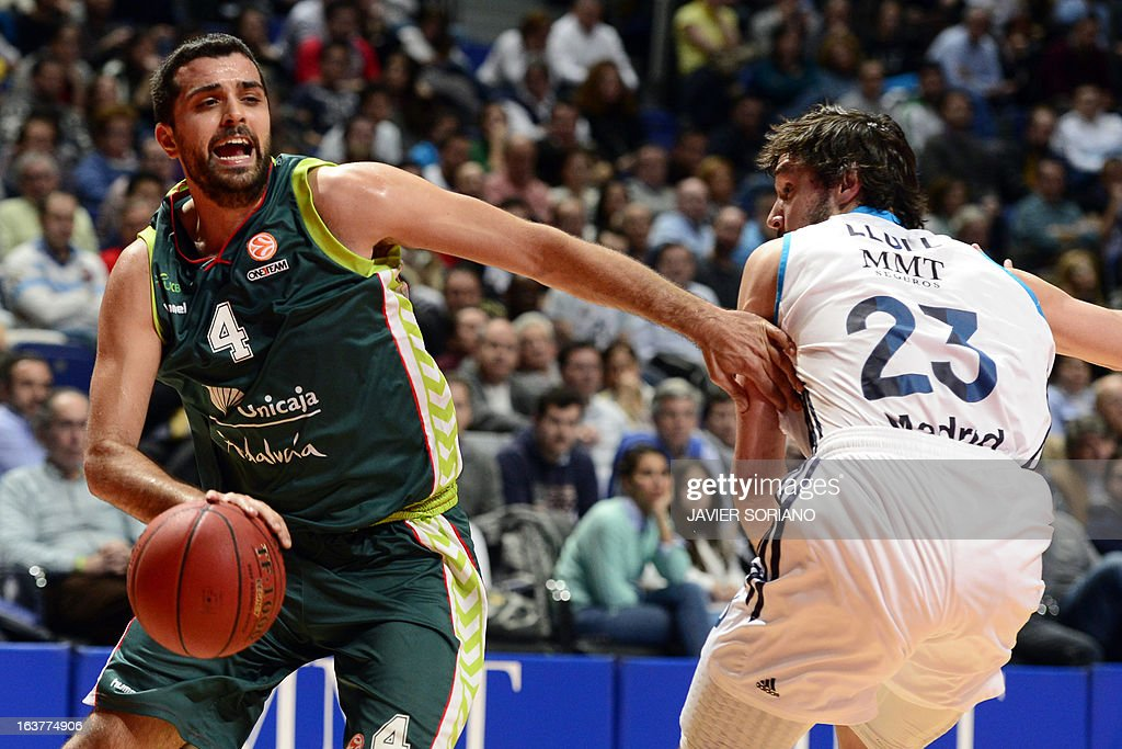 Unicaja's Croatian forward Krunoslav Simon (L) vies with Real Madrid's guard Sergio Llull during the Euroleague basketball match Real Madrid vs Unicaja at the Palacio de los Deportes in Madrid on March 15, 2013. AFP PHOTO/ JAVIER SORIANO