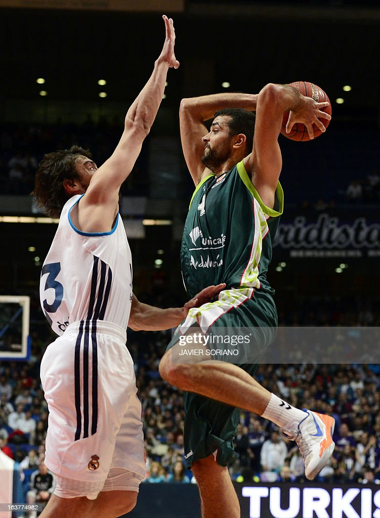 Unicaja's Croatian forward Krunoslav Simon (R) vies with Real Madrid's guard Sergio Llull during the Euroleague basketball match Real Madrid vs Unicaja at the Palacio de los Deportes in Madrid on March 15, 2013.