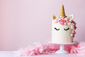 Unicorn cake with pink frosting and copy space to side