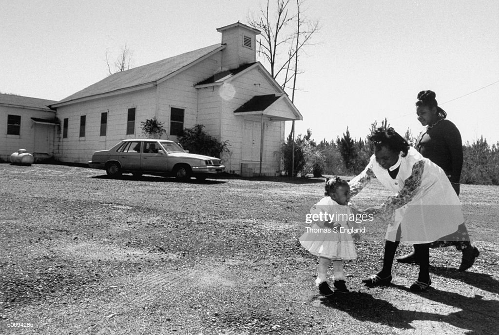 2 unident. African-American females & child walking outside St. Matthew's Baptist Church, re growing epidemic of arson commited against African-American churches in the south.