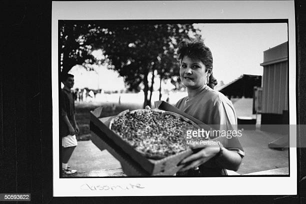 Unident white woman holding box of pizza prob knew Anita Hill who claimed that Supreme Court Justice Clarence Thomas sexually harassed her