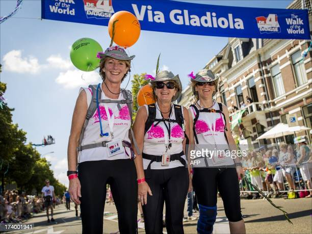 Unidentifed participants smile as they cross the finish line on July 19 2013 of the fourth and final day of the International Four Day Marches...
