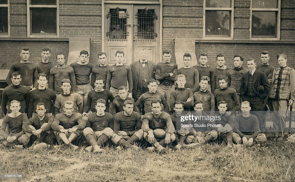 Unidentified 1913 football team from West Virginia posing in front of a brick building.