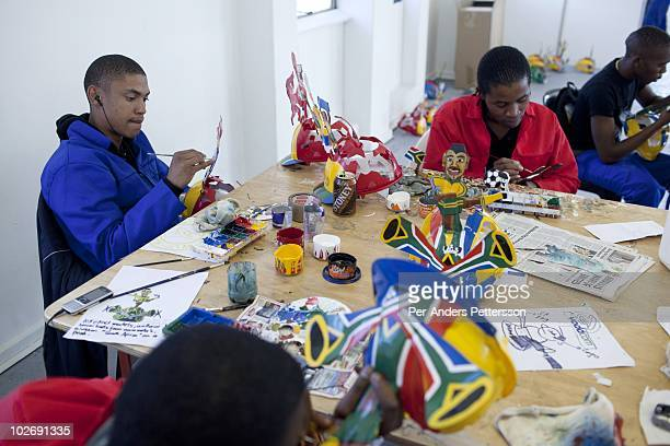 Unidentified artists paint Makarapa helmet before on May 10 in Alfred Baloyi's studio in Wynberg north of Johannesburg South Africa Mr Baloyi and a...