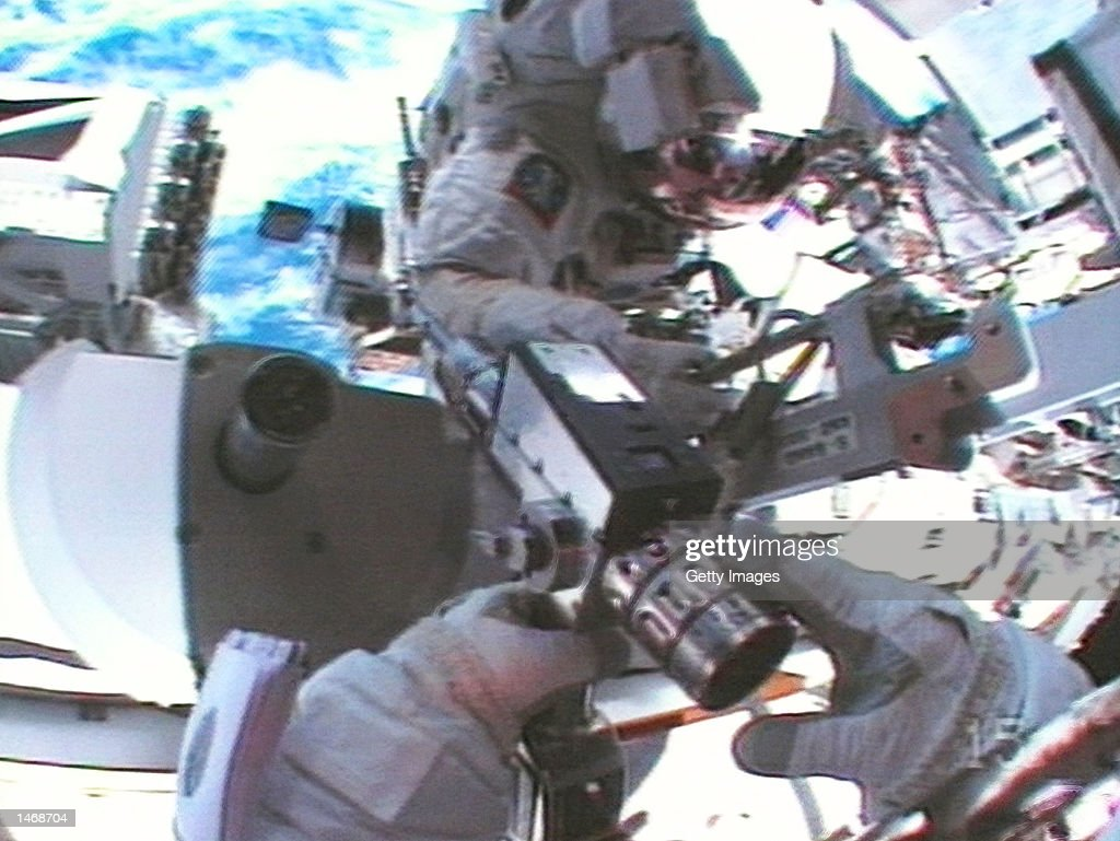 Unidentified astronauts work to attach a major new component to the International Space Station October 10 2002 The Space Shuttle Atlantis mission...
