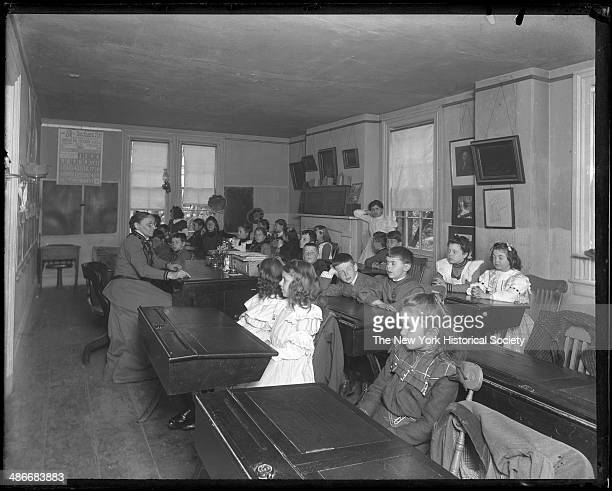 Unidentified children and teacher seated in a schoolroom 1895 Labelled 'JS Hall'