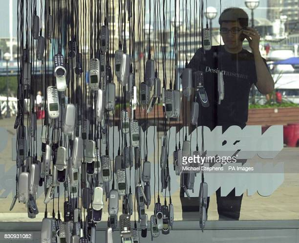 Unidentified Design Museum employee trying out a mobile phone at the Digital Aquarium on the riverfront terrace of the Design Museum by the Thames in...