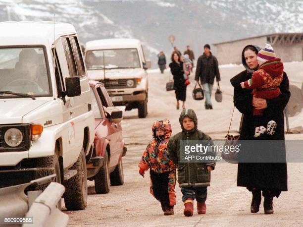 SKO01 19990220 BLACE MACEDONIA A unidentified ethnic Albanian woman with her children passes UN vehicles with members of humanitarian organizations...
