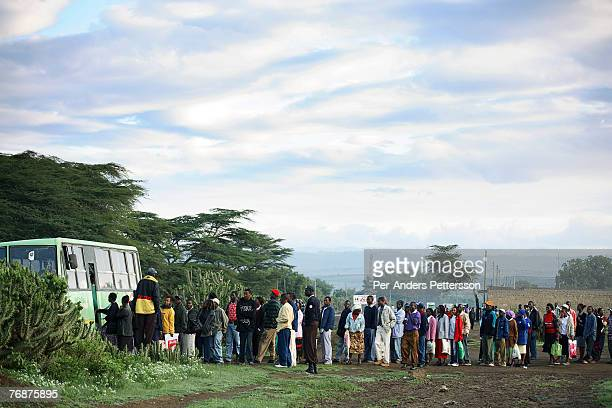Unidentified flower factory workers wait to board buses to take them to work on December 14 2006 in Lake Naivasha Kenya The area for years known as...
