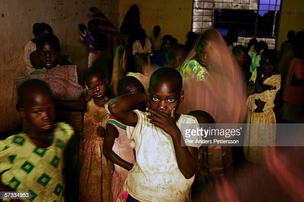 Unidentified girls collect their belongings after sleeping in a shelter on May 20 2005 in Gulu Uganda They are some of about 20000 night commuters...