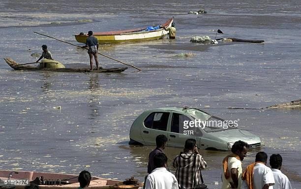 Unidentified Indian people watch the scene at the Marina beach in Madras 26 December 2004 after tidal waves hit the region Tidal waves devastated the...