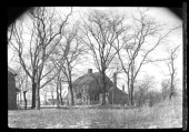 Unidentified large woodshake house with outbuildings seen through bare trees New York New York late 19th or early 20th century