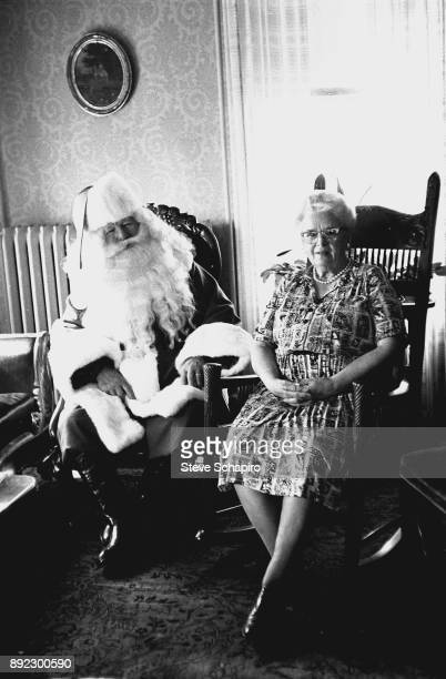 A unidentified man dressed as Santa Claus smiles as he sits next to a woman in a rocking chair Albion New York 1963