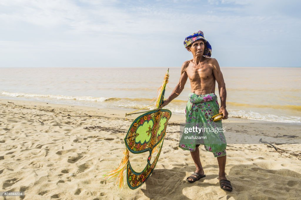 Unidentified man holding the traditional moon kite or locally known as 'Wau Bulan' in Kelantan : Stock Photo