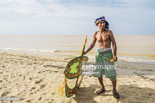 Unidentified man holding the traditional moon kite or locally known as 'Wau Bulan' in Kelantan : Stock Photo