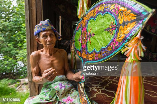 Unidentified man is making the traditional moon kite or locally known as 'Wau Bulan' at Kelantan, Malaysia. : Stock Photo