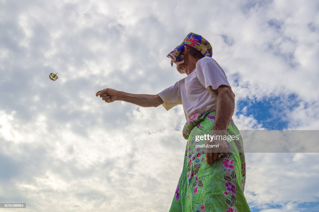 Unidentified man is playing the traditional moon kite or locally known as 'Wau Bulan' in Kelantan, Malaysia. : Stock Photo